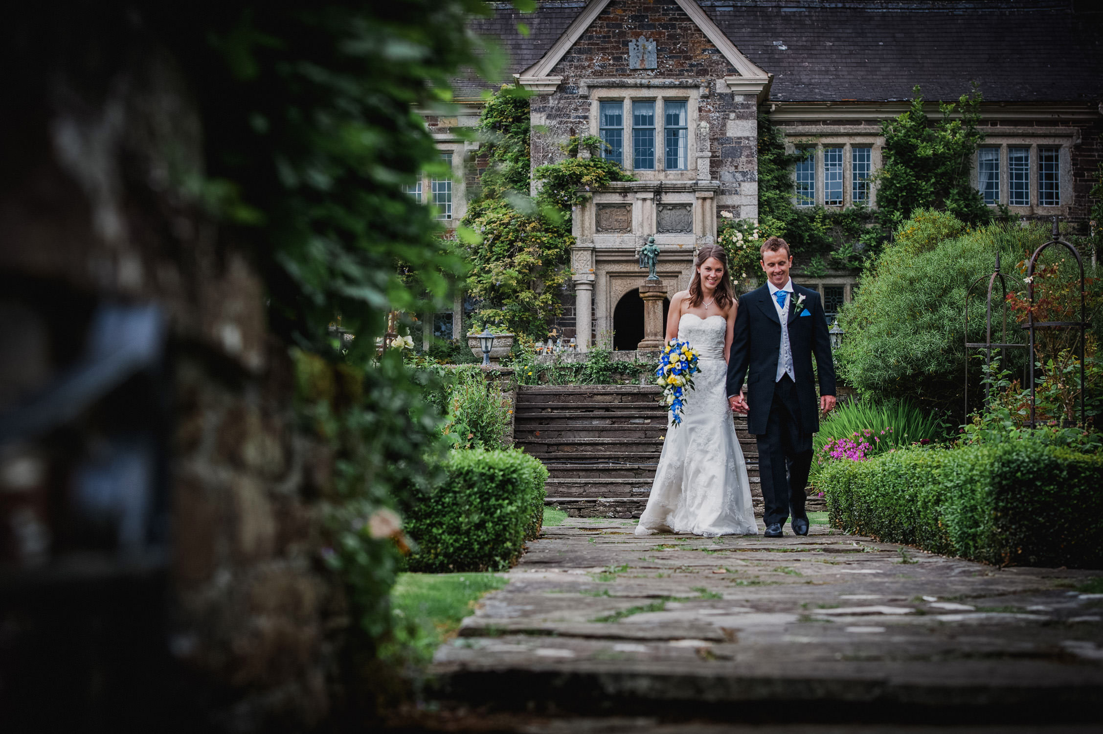 bride and groom walking down path at lewtrenchard manor wedding