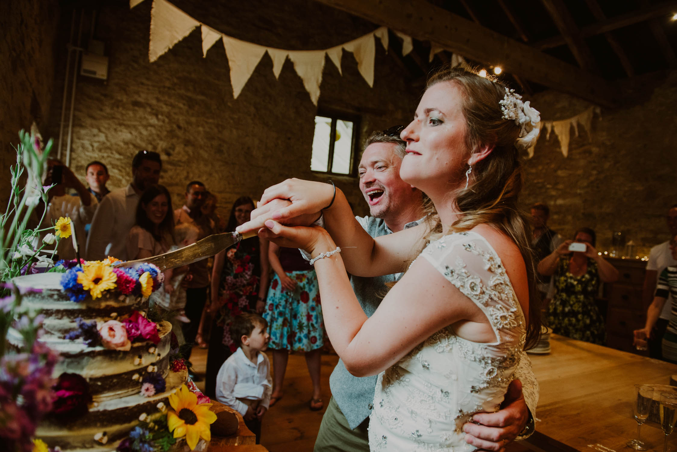 somerset wedding photographer capturing bride and groom cutting the cake, streamcombe farm wedding